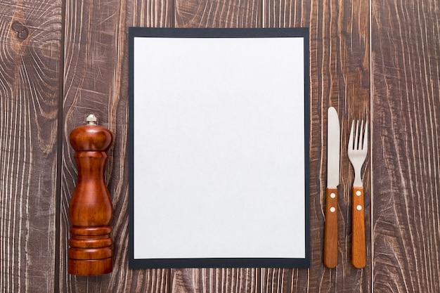Postura plana de papel de menu em branco com talheres na superfície de madeira
