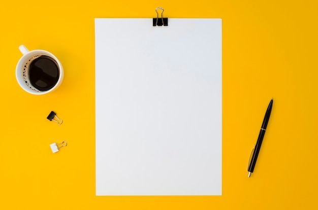 Postura plana de papel em branco com caneca de café