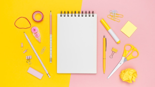 Postura plana de papelaria de escritório com notebook e elásticos