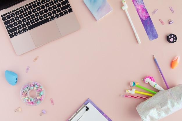 Postura plana de papelaria escolar elegante kawaii e laptop em rosa.