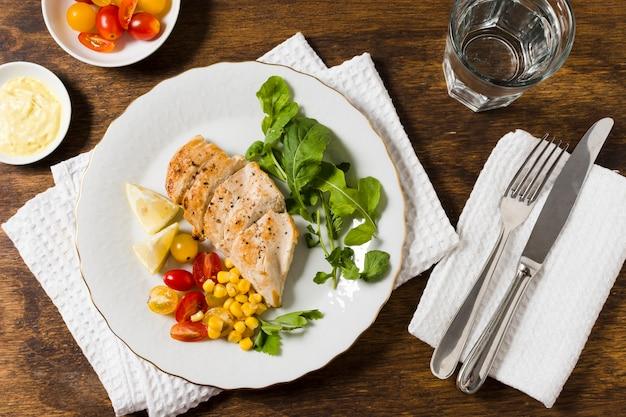 Postura plana de peito de frango com variedade de legumes