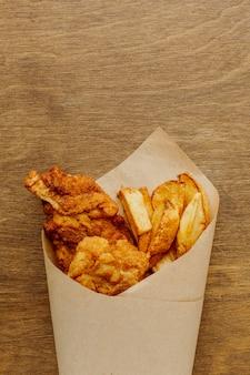 Postura plana de peixe e batatas fritas em embalagem de papel com espaço de cópia