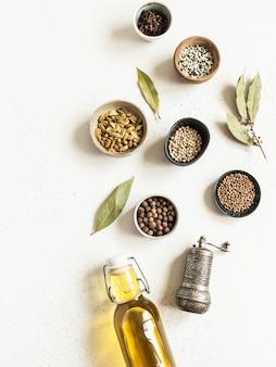 Postura plana de pequenas tigelas diversas especiarias secas e azeite em frasco de vidro