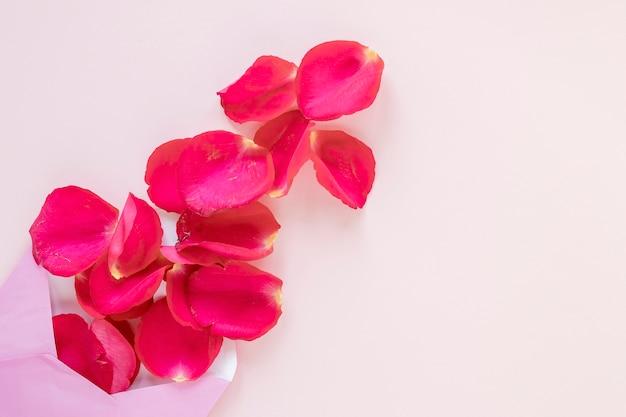 Postura plana de pétalas de rosa e envelope para dia dos namorados