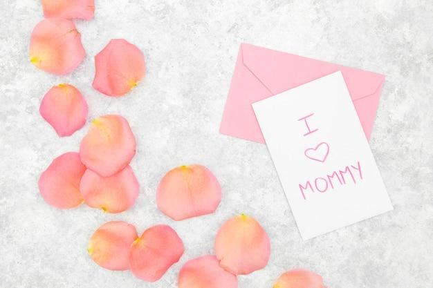 Postura plana de pétalas de rosas cor de rosa e envelope