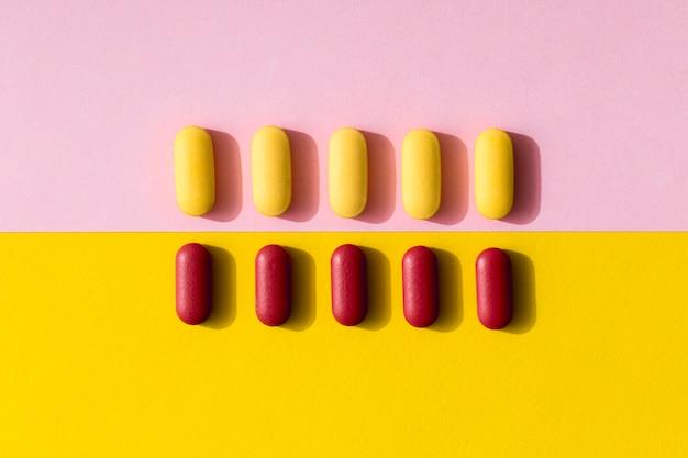 Postura plana de pílulas de cores diferentes em linhas
