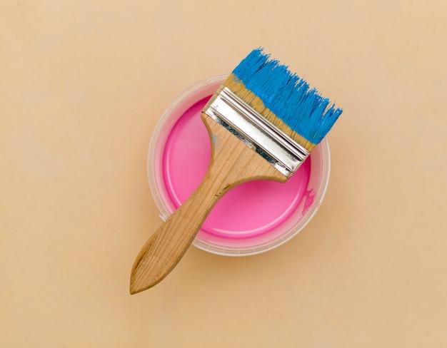 Postura plana de pincel azul e balde de tinta rosa