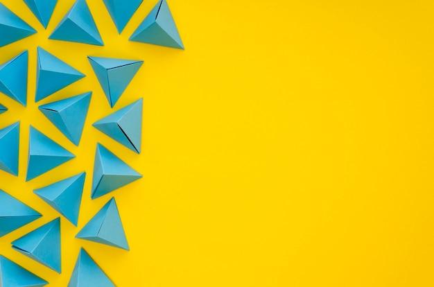Postura plana de pirâmides de papel colorido vibrante com espaço de cópia