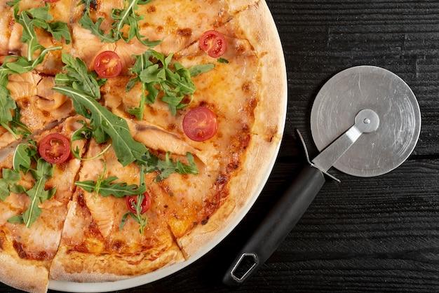 Postura plana de pizza com rúcula e tomate cereja na mesa de madeira
