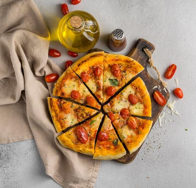 Postura plana de pizza cortada em fatias com tomate e óleo