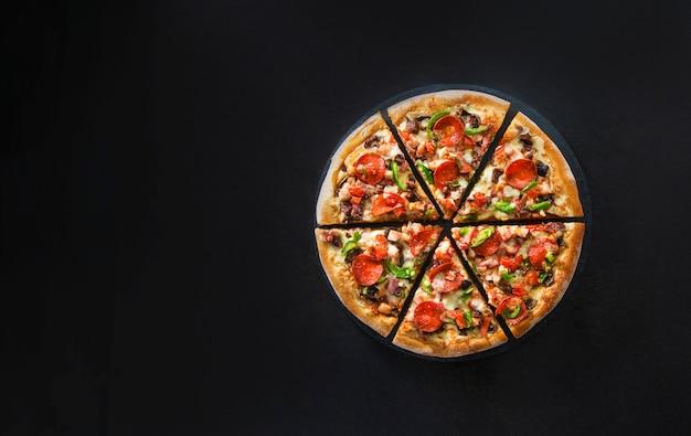 Postura plana de pizza italiana na vista superior da superfície escura