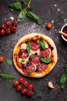 Postura plana de pizza recém-assada com azeitonas, manjericão e ingredientes em um fundo preto