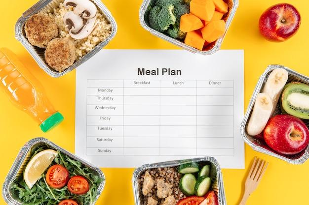 Postura plana de plano de refeições com caçarolas com frutas e legumes