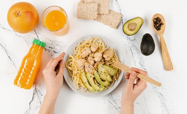 Postura plana de prato com macarrão e abacate