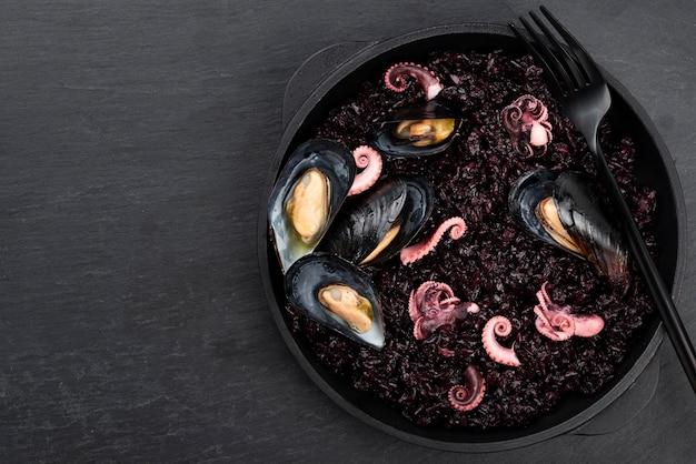 Postura plana de prato com macarrão preto e mexilhões