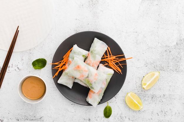 Postura plana de prato com rolos de camarão e cenoura
