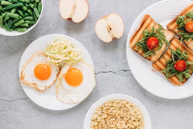 Postura plana de pratos com ovos fritos e maçãs