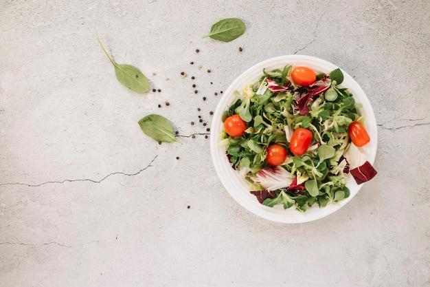 Postura plana de pratos com salada e espinafre