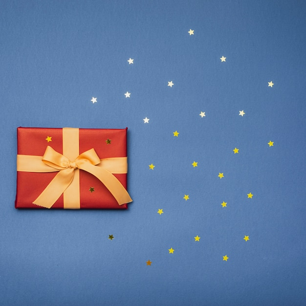Postura plana de presente de natal com estrelas douradas