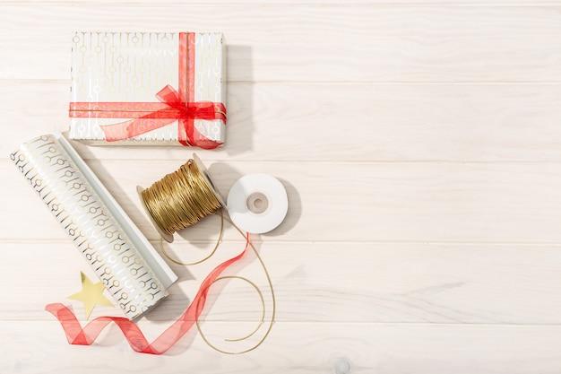Postura plana de presentes de natal, papel de decoração, fitas e tesouras.