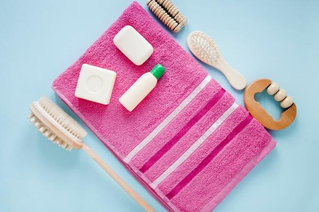 Postura plana de produtos de banho na toalha rosa