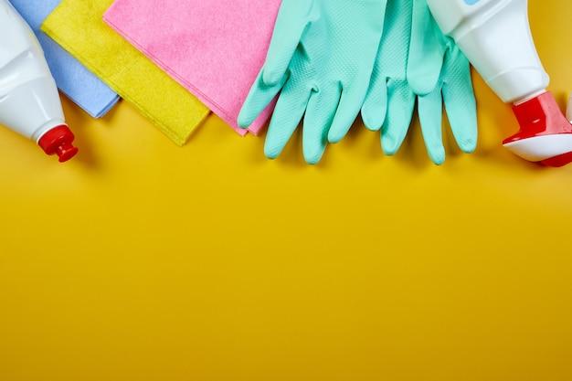 Postura plana de produtos de limpeza de casa de variedades na mesa amarela com espaço de cópia, conjunto de limpeza para superfícies diferentes, conceito de serviço de detergentes, vista superior.