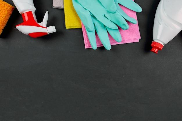Postura plana de produtos de limpeza de casa de variedades na mesa preta com espaço de cópia, conjunto de limpeza para superfícies diferentes, conceito de serviço de detergentes, vista superior.