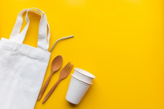 Postura plana de produtos sustentáveis, madeira e palha de aço inoxidável em saco de pano amarelo