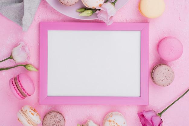 Postura plana de quadro com macarons e rosas
