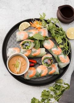 Postura plana de rolos de camarão no prato com molho