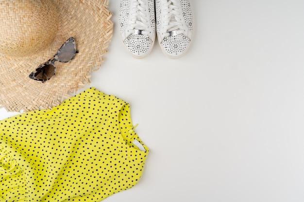 Postura plana de roupa de verão mulher na superfície branca