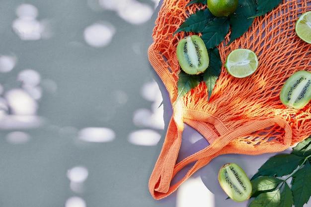 Postura plana de saco de compra de malha amigável de eco com frutas limão e kiwi em fundo cinza na luz solar, horário de verão. conceito de mercearia, cópia espaço, vista superior.