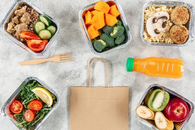 Postura plana de saco de papel com refeições em caçarolas e suco de laranja