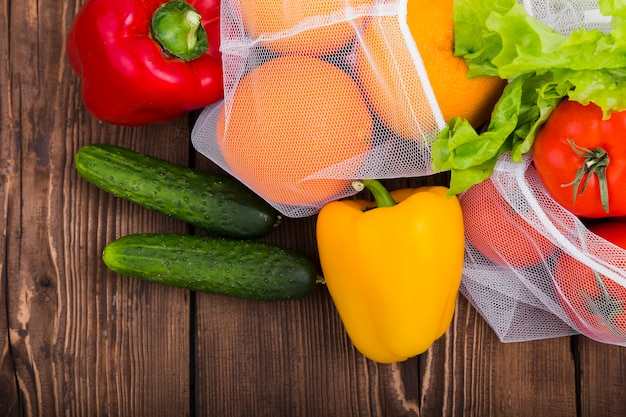 Postura plana de sacos reutilizáveis na superfície de madeira com frutas e legumes