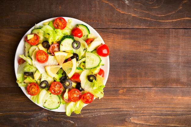 Postura plana de salada verde e vermelha com limão e sementes em fundo de madeira