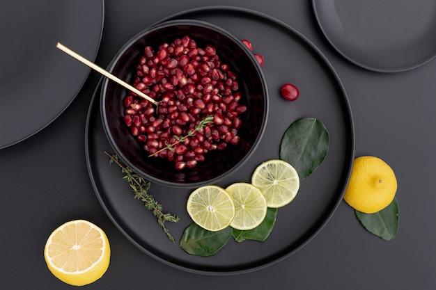 Postura plana de sementes de romã em uma tigela com rodelas de limão