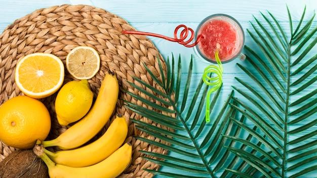 Postura plana de smoothie e frutas na mesa de madeira