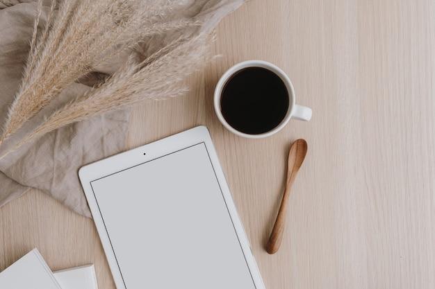 Postura plana de tablet de tela em branco, xícara de café, grama de pampas em madeira bege. espaço de trabalho da mesa do escritório em casa. camada plana, vista superior.