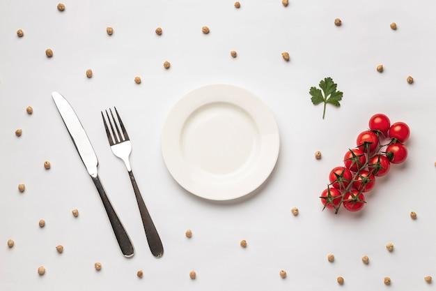Postura plana de tomates frescos com prato e talheres