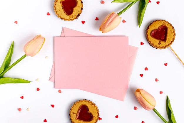 Postura plana de tulipas e biscoitos com papéis para dia dos namorados
