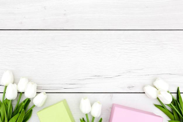 Postura plana de tulipas na mesa de madeira