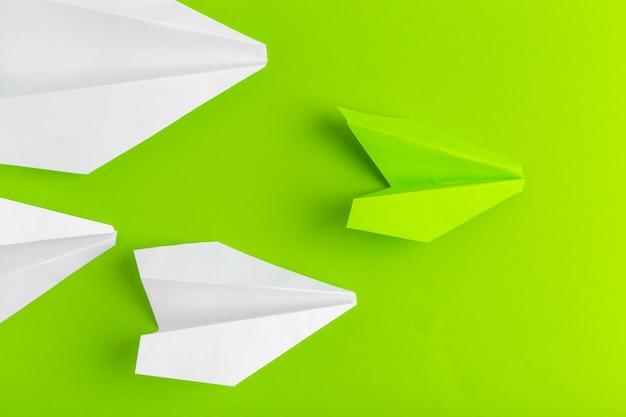 Postura plana de um avião de papel na cor pastel verde