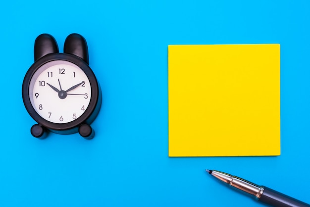 Postura plana de um papel para anotações em branco e despertador para escrever mensagens