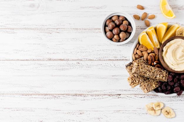 Postura plana de variedade de nozes no prato com barras de cereais