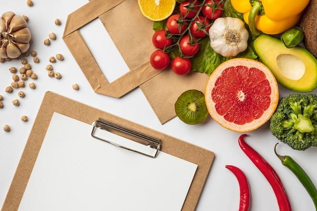 Postura plana de variedade de vegetais com saco de papel e prancheta