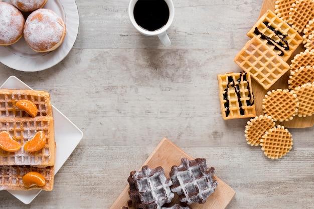 Postura plana de variedade de waffles com café e rosquinhas
