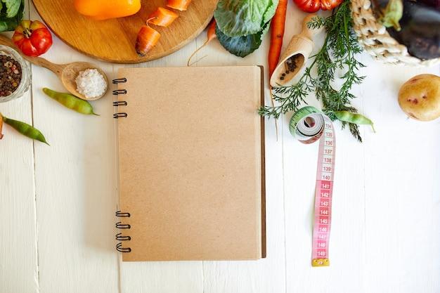 Postura plana de vários ingredientes de vegetais orgânicos e fita métrica na superfície de madeira, comida vegetariana e vegan, conceito de dieta primavera, vista superior, espaço de cópia.