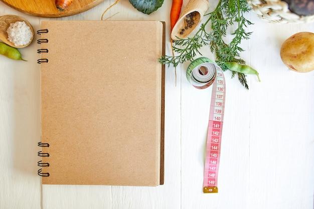 Postura plana de vários ingredientes de vegetais orgânicos e fita métrica na superfície de madeira