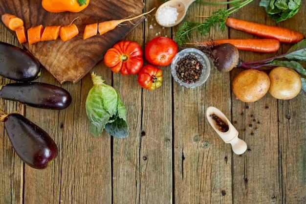 Postura plana de vários ingredientes vegetais orgânicos e picantes na superfície de madeira