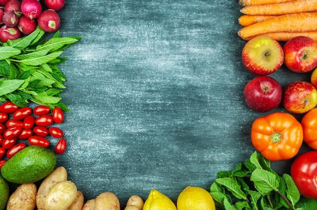 Postura plana de vegetais crus multicoloridos em um fundo preto, quadro de comida. produtos locais para uma cozinha saudável. frutas e vegetais orgânicos para a vegetação. vista do topo. copie o espaço.